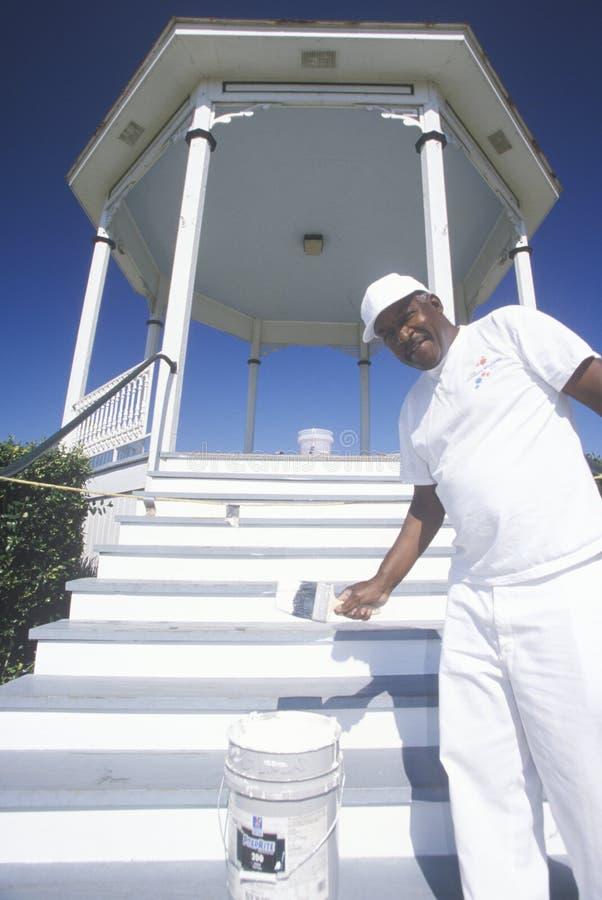 O afro-americano em Natchez, MS pinta o miradouro com o revestimento novo da pintura branca imagem de stock royalty free