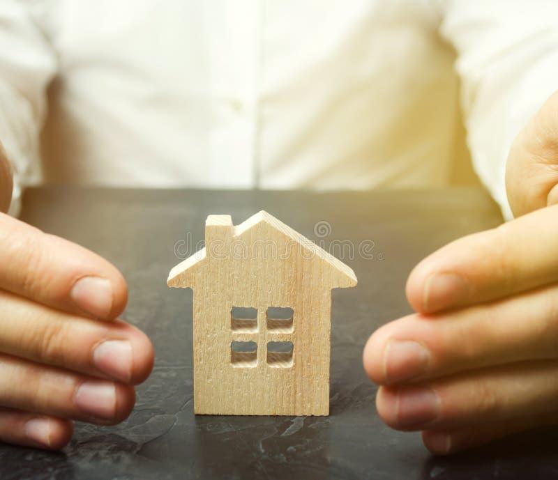 O agente de seguros protege a casa com um gesto da prote??o O conceito do seguro patrimonial e do alojamento Seguran?a e imagem de stock royalty free