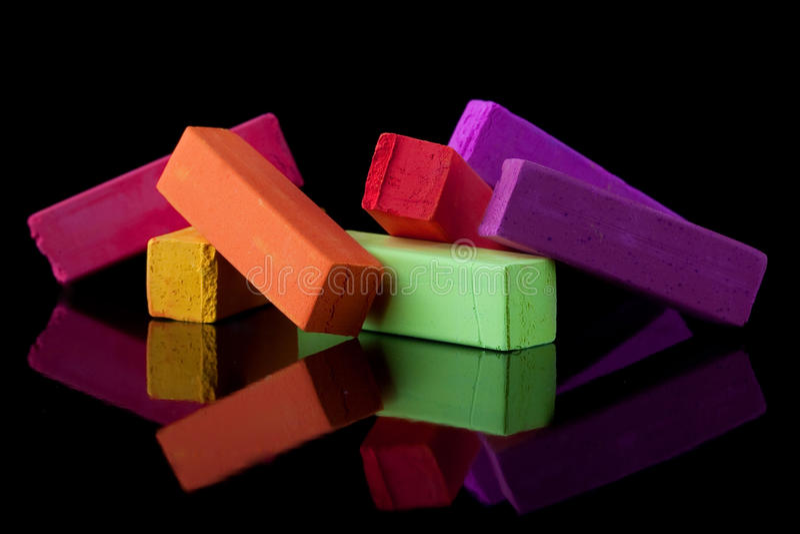 O agrupamento do giz colorido fura no backgro preto imagem de stock royalty free