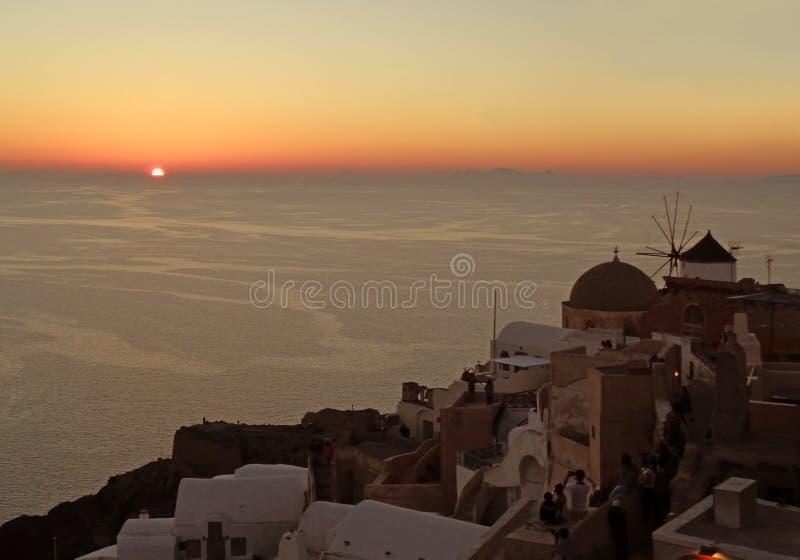 O ajuste do sol no horizonte vila do Mar Egeu, Oia, ilha de Santorini, Grécia imagens de stock