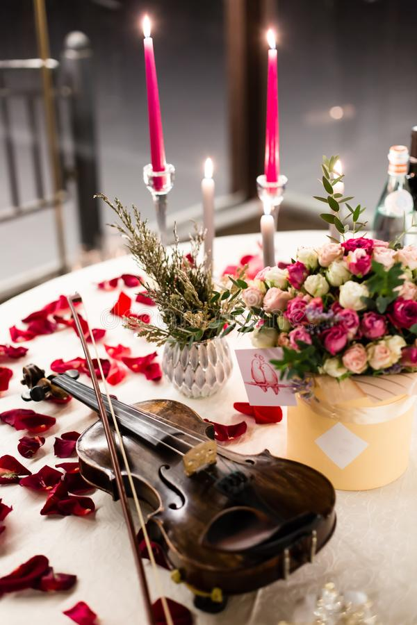 O ajuste romântico da tabela com as flores bonitas na caixa, aumentou as pétalas e o violino fotografia de stock