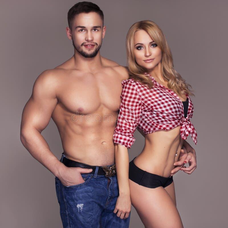 O ajuste 'sexy' muscled pares nas calças de brim e nas calças e no t-shirt da manta sobre fotos de stock