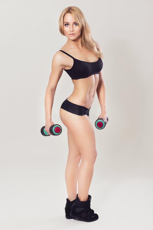 O ajuste 'sexy' muscled pares no sportswear no fundo cinzento neutro imagens de stock
