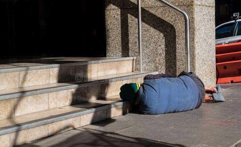 O alcoólico está dormindo na rua fotografia de stock