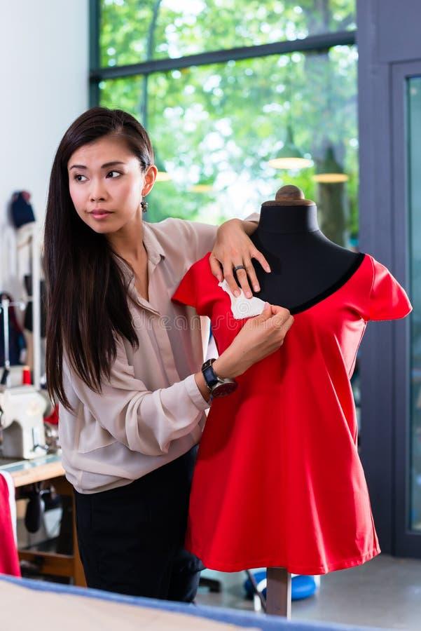 O alfaiate asiático ajusta o projeto do vestuário no manequim foto de stock