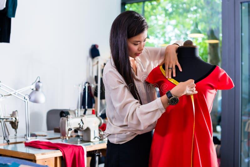O alfaiate asiático ajusta o projeto do vestuário no manequim imagens de stock royalty free