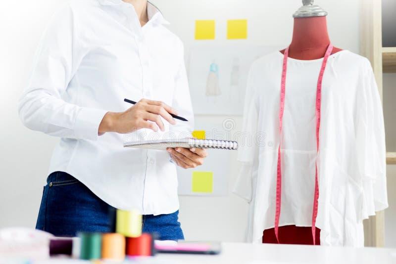 O alfaiate asiático ajusta o projeto do vestuário no manequim no valor máximo de concentração no trabalho da oficina foto de stock royalty free