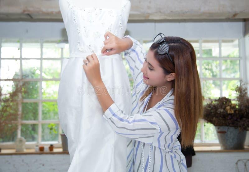 O alfaiate asiático novo ajusta o vestido de medição do projeto do vestuário no A M. imagens de stock royalty free