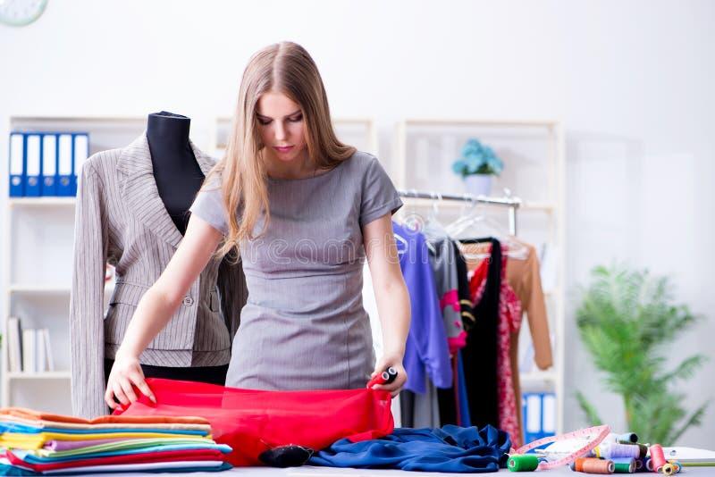 O alfaiate da jovem mulher que trabalha na oficina no vestido novo fotografia de stock royalty free