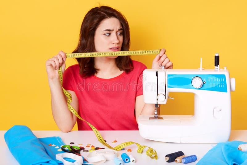 O alfaiate da mulher que trabalha na máquina de costura da roupa, guardando a medida da fita, olhando de lado, tem a expressão fa foto de stock royalty free