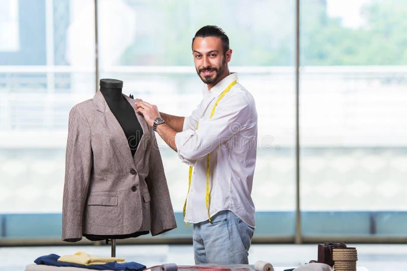 O alfaiate novo que trabalha no projeto novo da roupa fotografia de stock royalty free