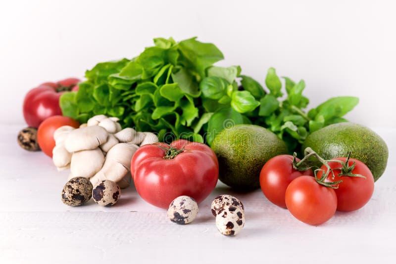 O alimento da dieta saudável nos ovos brancos dos cogumelos das folhas do verde das pimentas dos tomates dos vegetais do fundo fa imagem de stock