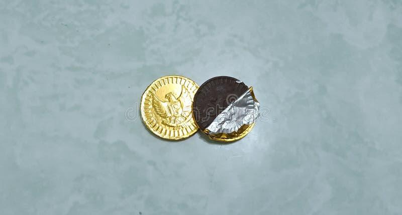 O alimento das crianças sob a forma do chocolate envolvido na rupia indonésia da moeda imagens de stock