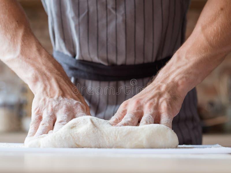 O alimento de Breadbaking que cozinha as mãos do homem amassa a massa foto de stock