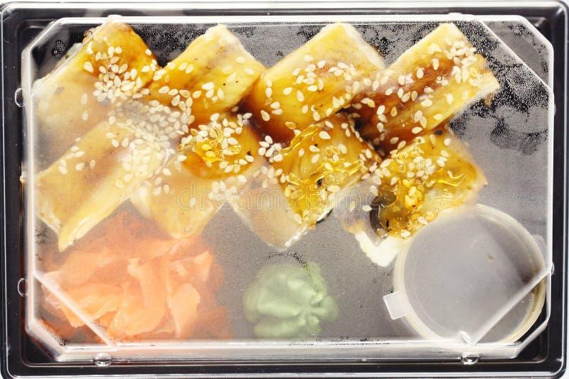 O alimento japonês do serviço de entrega rola na caixa plástica foto de stock royalty free