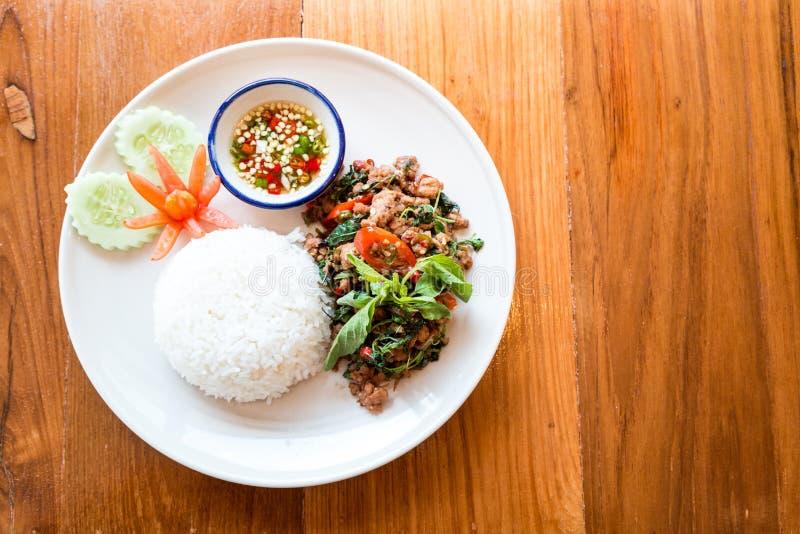 O alimento tailandês, agitação fritou a carne de porco com a manjericão que come com arroz fotografia de stock royalty free