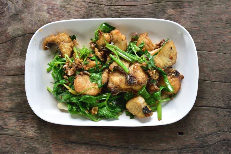 O alimento tailandês delicioso, peixe da caranga fritou o aipo no prato branco fotos de stock