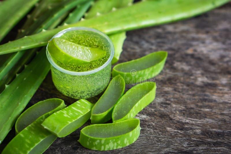 O aloés verde fresco vera deixa o gel de vera da fatia e do aloés na tabela de madeira fotos de stock
