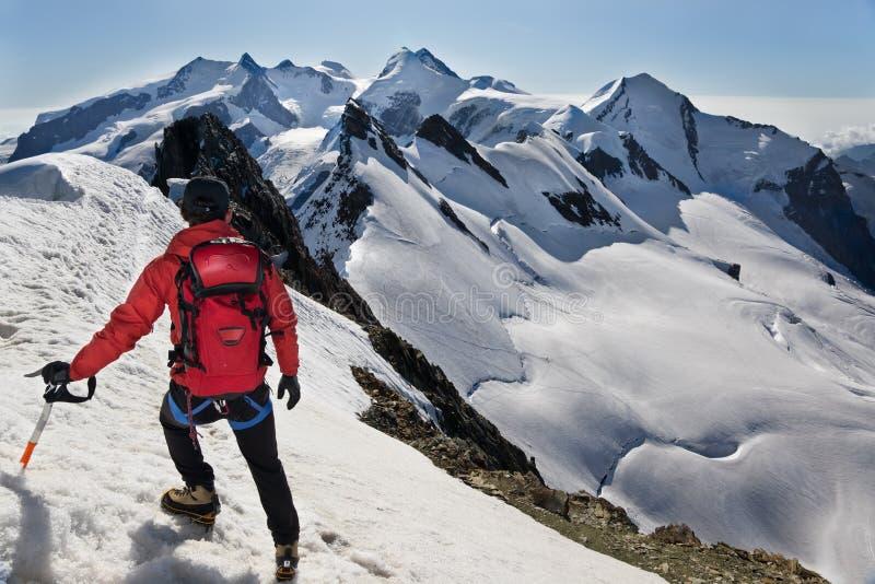 O alpinista anda para baixo ao longo de um cume nevado imagem de stock