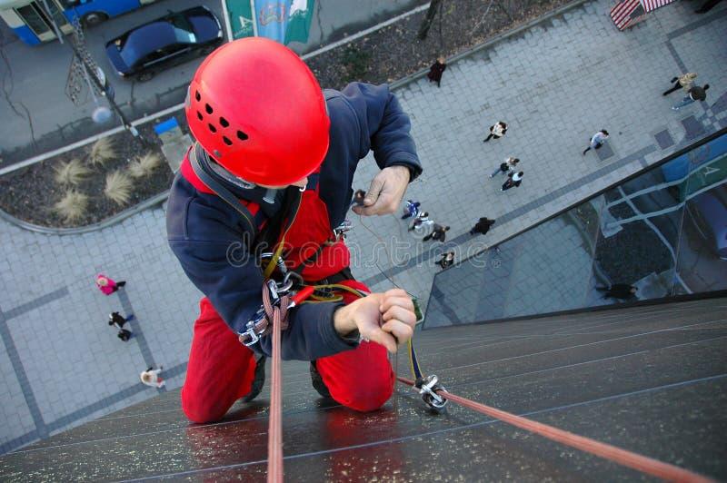 O alpinista escala a construção imagem de stock