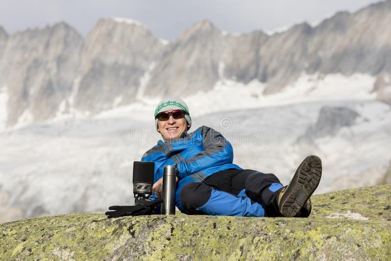 O alpinista faz uma ruptura de chá antes dos Mountain View excitantes fotos de stock royalty free