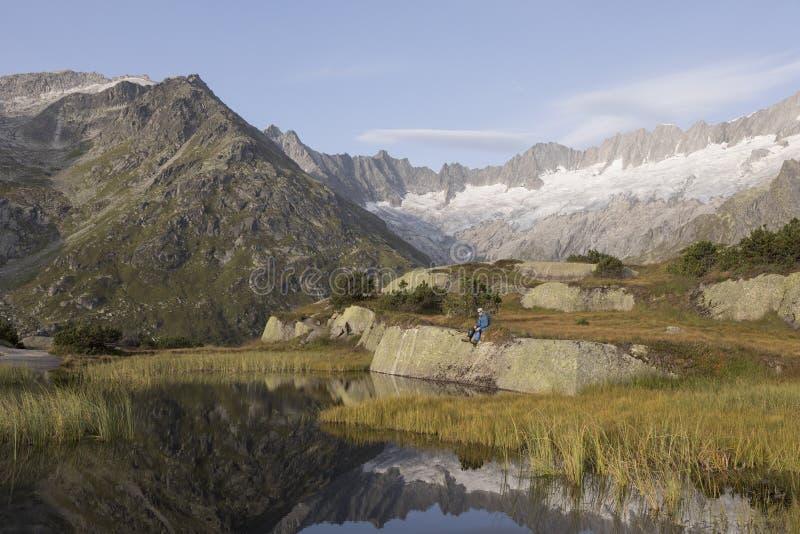 O alpinista faz uma ruptura durante um nascer do sol em um lago da montanha nos cumes fotos de stock