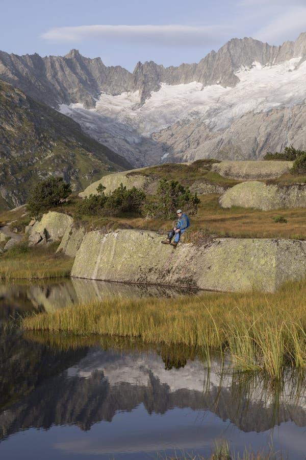 O alpinista faz uma ruptura durante um nascer do sol em um lago da montanha nos cumes foto de stock