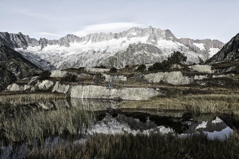 O alpinista faz uma ruptura durante um nascer do sol em um lago da montanha nos cumes fotos de stock royalty free