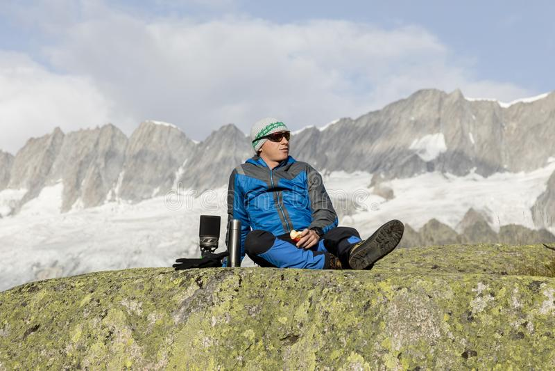 O alpinista faz uma ruptura nas montanhas e come uma maçã imagens de stock