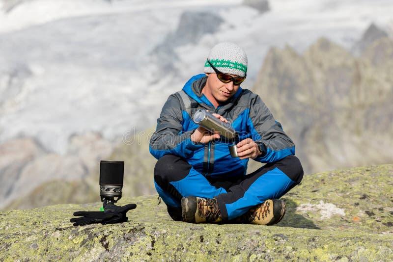 O alpinista faz uma ruptura nas montanhas e derrama um chá imagem de stock royalty free