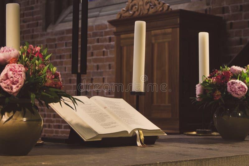O altar bonito na catedral católica desvaneceu-se A Bíblia Sagrada aberta com flores, velas e cruz Decoração elegante da igreja imagens de stock royalty free