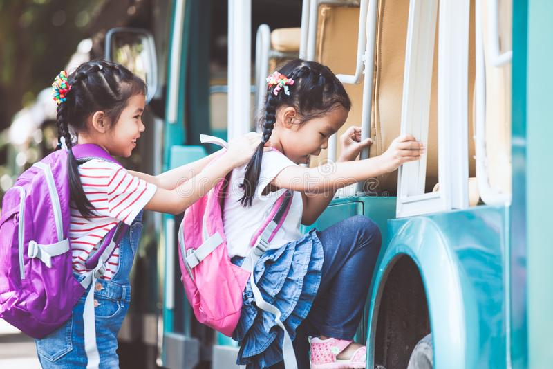 O aluno asiático caçoa com a trouxa que guarda a mão e que vai à escola foto de stock