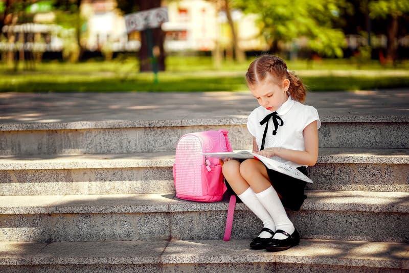 O aluno da escola primária leu o assento do livro em escadas Menina com a trouxa perto da constru??o fora Come?o das li??es fotografia de stock royalty free