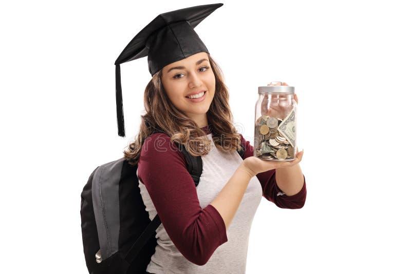 O aluno diplomado alegre que guarda um frasco encheu-se com o dinheiro fotos de stock royalty free