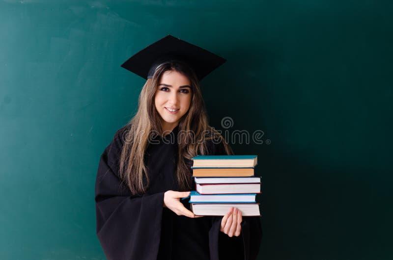 O aluno diplomado f?mea na frente da placa verde foto de stock royalty free