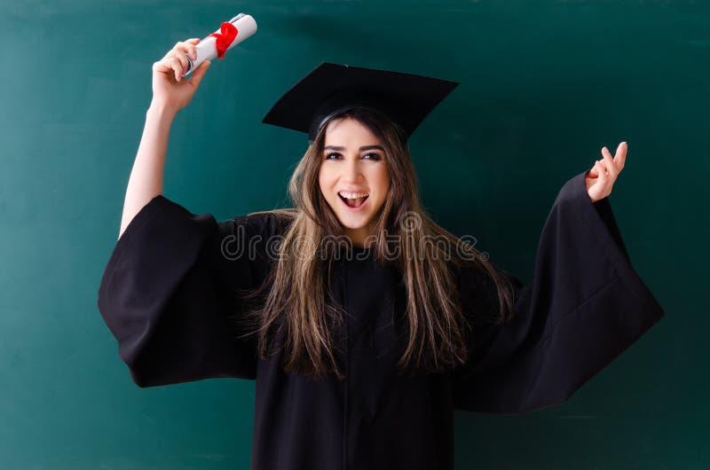O aluno diplomado f?mea na frente da placa verde foto de stock
