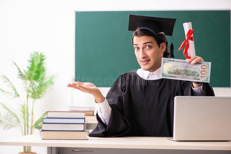 O aluno diplomado na frente da placa verde foto de stock