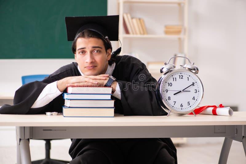 O aluno diplomado na frente da placa verde imagens de stock royalty free