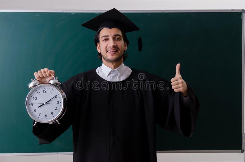 O aluno diplomado na frente da placa verde imagens de stock