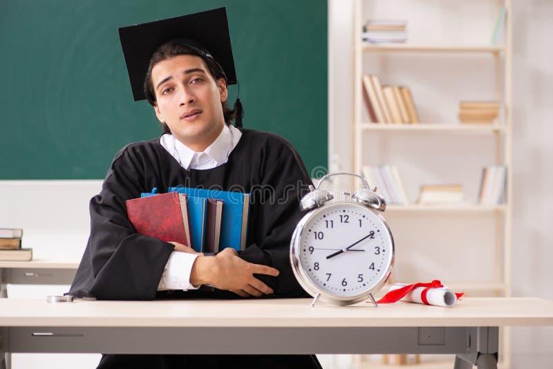 O aluno diplomado na frente da placa verde foto de stock royalty free