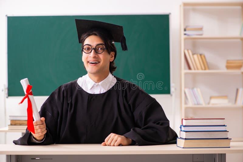 O aluno diplomado na frente da placa verde fotografia de stock royalty free