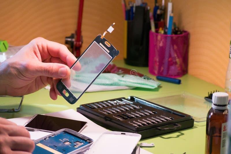 O amador está tentando mudar o écran sensível quebrado do smartphone fotos de stock