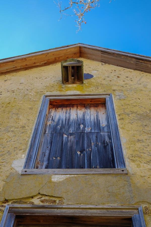 O amarelo alto emplastrou a estrutura colonial com janelas coloridas r foto de stock royalty free