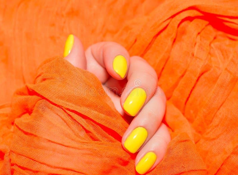 O amarelo bonito prega o tratamento de mãos Tratamento de mãos claro na luz em um fundo branco foto de stock royalty free