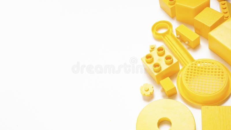 O amarelo brinca a opinião superior do fundo no branco Quadro dos brinquedos das crianças no fundo branco Vista superior Configur imagem de stock