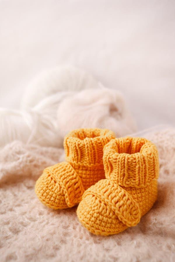 O amarelo do ` s das crianças fez malha montantes em um fundo delicado claro O conceito de esperar uma criança, maternidade, pate foto de stock