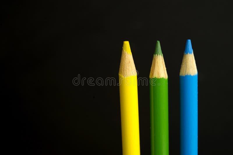 O amarelo, verde e o azul coloriram pastéis do lápis em um backgr preto fotografia de stock