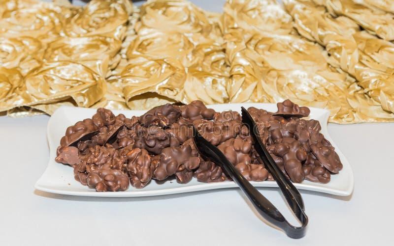 O amendoim do chocolate aglomera o arranjo no branco e no partido temático do ouro imagem de stock royalty free