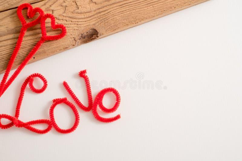 O amor é uma palavra é escrito que soletra a fonte O vermelho do amor da palavra Fundo branco, tabela de madeira Espaço para o te fotos de stock