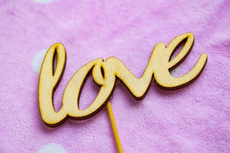 O amor da palavra é feito de letras de madeira em um fundo cor-de-rosa com ervilhas brancas Conceito do dia do ` s do Valentim, v foto de stock royalty free